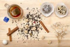 Taza con la bolsita de té y la torta Imagen de archivo libre de regalías