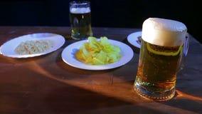 Taza con la cerveza ligera espumosa en una tabla de madera en un fondo negro metrajes