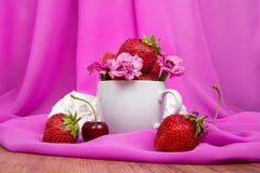 Taza con las fresas, flores, cerezas en un fondo Fotografía de archivo libre de regalías