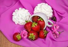 Taza con las fresas, flores, cerezas en un fondo Imagen de archivo