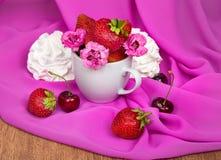 Taza con las fresas, flores, cerezas en un fondo Imagenes de archivo