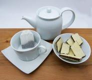 Taza con las obleas de las bolsitas de té, de la tetera y del chocolate en la tabla de madera, fondo blanco fotografía de archivo