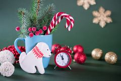 Taza con los abetos, bastones de caramelo y reloj y galletas rojos en la forma de un perro Imagen de archivo