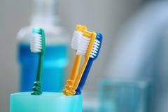 Taza con los cepillos de dientes en fondo Fotos de archivo