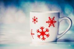 Taza con los copos de nieve en fondo del bokeh del invierno imagen de archivo libre de regalías