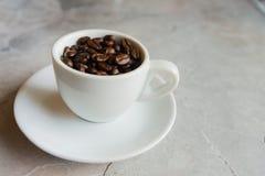 Taza con los granos de café Foto de archivo libre de regalías