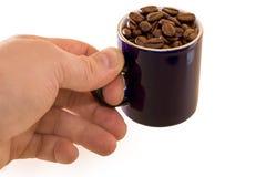 Taza con los granos de café a disposición aislados Foto de archivo