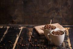 Taza con los granos de café en el fondo de madera oscuro Foto de archivo libre de regalías