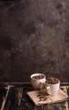 Taza con los granos de café en el fondo de madera oscuro Fotografía de archivo