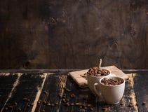Taza con los granos de café en el fondo de madera oscuro Imagenes de archivo