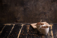 Taza con los granos de café en el fondo de madera oscuro Foto de archivo