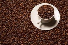 Taza con los granos de café en un fondo oscuro Imágenes de archivo libres de regalías