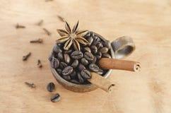 Taza con los granos de café, los palillos de canela y el anís de estrella en una tabla de madera Foco selectivo fotos de archivo