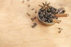 Taza con los granos de café, los palillos de canela y el anís de estrella en una tabla de madera Foco selectivo foto de archivo libre de regalías