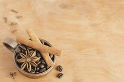 Taza con los granos de café, los palillos de canela y el anís de estrella en una tabla de madera Foco selectivo foto de archivo