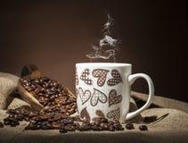 Taza con los granos del corazón y de café en fondo oscuro fotos de archivo libres de regalías