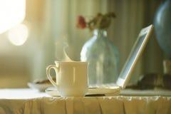 Taza con té caliente cerca del ordenador Tiempo del café Fotografía de archivo