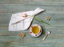 Taza con té y el tulipán Imagen de archivo libre de regalías