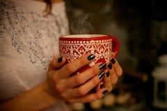 Taza con una bebida que se calienta en muchachas de las manos Fotos de archivo libres de regalías