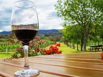 Taza cristalina con el vino en la tabla de madera con las montañas, los árboles, los viñedos y el fondo de las flores foto de archivo libre de regalías
