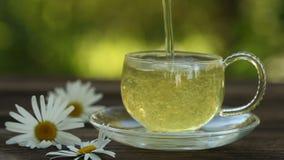Taza cristalina con té verde en la tabla metrajes