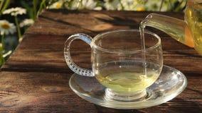 Taza cristalina con té verde en la tabla almacen de video