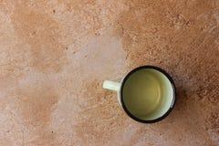 Taza de acero africana en un piso del cemento Imagenes de archivo