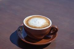 Taza de arte del capucino del café en la tabla de madera Foto de archivo libre de regalías