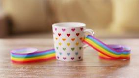 Taza de bebida caliente con la cinta de la conciencia del orgullo gay almacen de metraje de vídeo