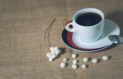 Taza de bebida caliente con los granos de café Imagenes de archivo