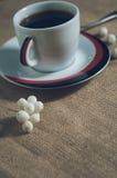 Taza de bebida caliente con los granos de café Fotografía de archivo