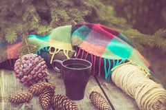 Taza de bebida caliente en una tabla de madera rústica Todavía la vida de conos, guita, bramante, abeto ramifica Preparación para Imagen de archivo libre de regalías