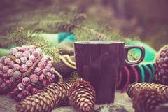 Taza de bebida caliente en una tabla de madera rústica Todavía la vida de conos, guita, bramante, abeto ramifica Preparación para Imagenes de archivo