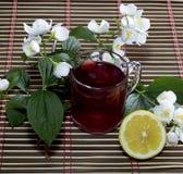 Taza de bebida roja, del limón y de flor, aún vida del corte Imágenes de archivo libres de regalías