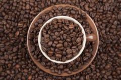 Taza de Brown con café en los granos de café foto de archivo libre de regalías