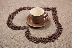 Taza de Brown en de arpillera con el corazón del café imagen de archivo