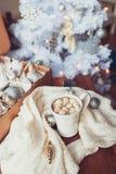 Taza de cacao caliente con la melcocha con las decoraciones de la Navidad en casa, árbol de navidad en fondo Foto de archivo