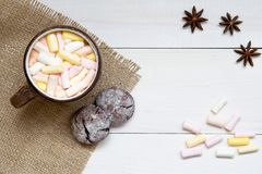 Taza de cacao caliente con las melcochas y las galletas en la tabla blanca, visión superior, espacio de la copia imagen de archivo
