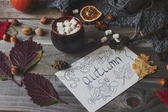 Taza de cacao con la melcocha, la postal hecha en casa del otoño, las hojas de la caída, la calabaza y las nueces en fondo de mad Imágenes de archivo libres de regalías
