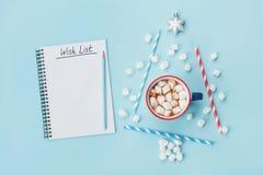 Taza de cacao o de chocolate caliente, árbol de abeto elegante y list d'envie en la opinión superior del fondo azul Concepto de l Fotos de archivo libres de regalías