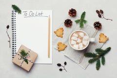 Taza de cacao o de chocolate caliente con la melcocha, las galletas y el cuaderno con la Navidad para hacer la lista en la tabla  Imagen de archivo libre de regalías