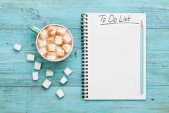 Taza de cacao o de chocolate caliente con la melcocha y el cuaderno con para hacer la lista en la tabla del vintage de la turques Fotografía de archivo