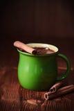 Taza de cacao y de canela en una tabla de madera Foto de archivo