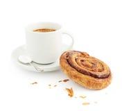 Taza de café al lado del bollo de canela Imagen de archivo libre de regalías