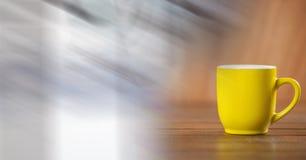 Taza de café amarilla con la transición blanca borrosa Imágenes de archivo libres de regalías