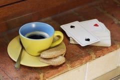 Taza de café amarilla con las galletas y una cubierta de las tarjetas dos de espadas fotografía de archivo