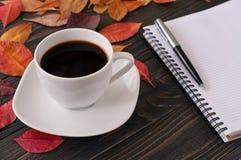 Taza de café americana con las hojas, el cuaderno y la pluma de otoño Foto de archivo