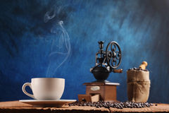 Taza de café, amoladora de café, granos de café en un saco Imagenes de archivo