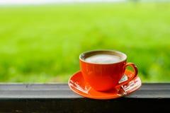 Taza de café anaranjada con el bokeh de la naturaleza Imagen de archivo
