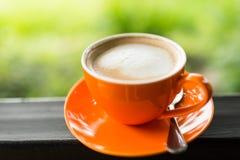 Taza de café anaranjada con el bokeh de la naturaleza Foto de archivo